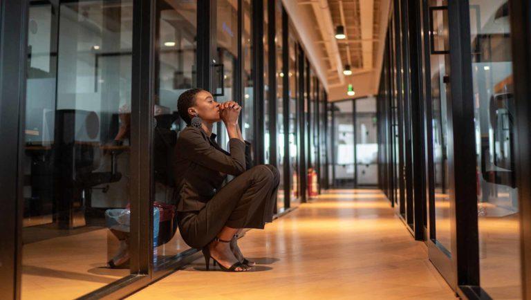 Depressed employee in empty office hallway
